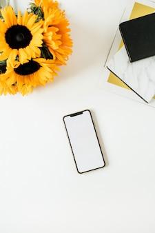 Area di lavoro scrivania da casa con smart phone, notebook, bouquet di girasoli gialli su bianco