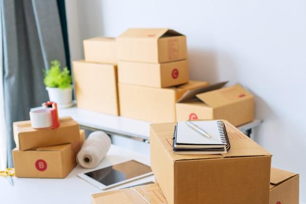 Home office del venditore di attività online di avvio, che mostra la tabella con scatole di cartone, tablet, smartphone, notebook e attrezzature. vendita online, imprenditore, concetto di lavoro da / a casa.
