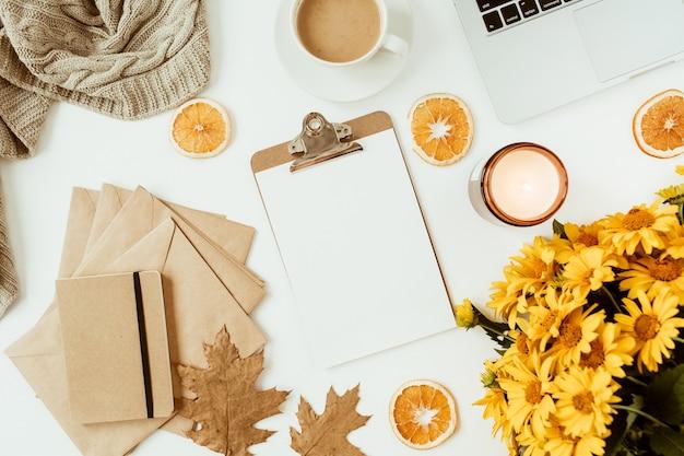 Area di lavoro scrivania tavolo da ufficio con appunti decorata con bouquet di fiori margherita gialla, tazza di caffè, fette d'arancia, plaid. vista piana laico e dall'alto