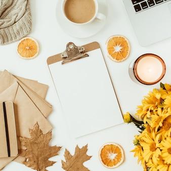 Area di lavoro scrivania tavolo da ufficio con appunti decorata con bouquet di fiori margherita gialla, tazza di caffè, fette d'arancia, plaid