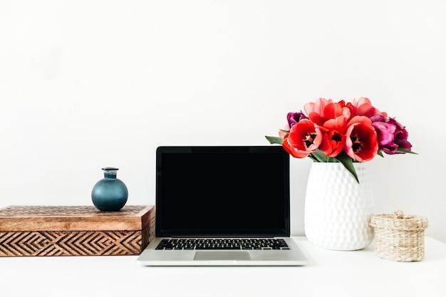 Ministero degli interni con laptop copia spazio, bouquet di fiori di tulipano, decorazioni su bianco