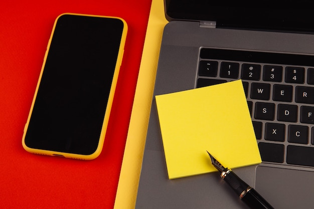 Concetto di scrivania sul posto di lavoro dell'ufficio domestico. laptop, smartphone e penna con nota adesiva gialla su sfondo rosso.