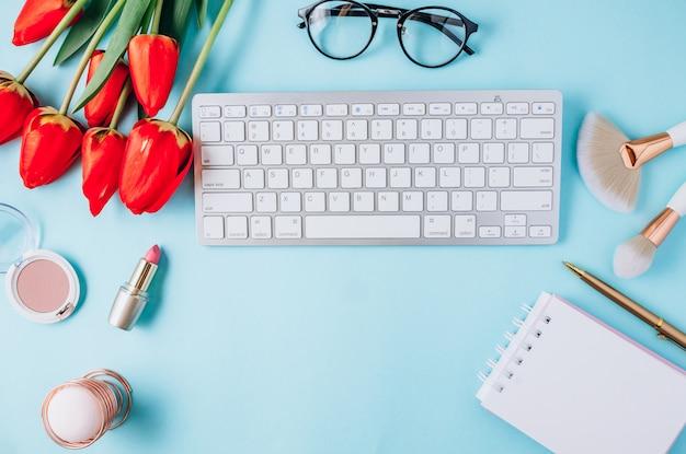 Luogo di lavoro a casa: taccuino vuoto, occhiali da vista, tastiera, fiori di tulipano