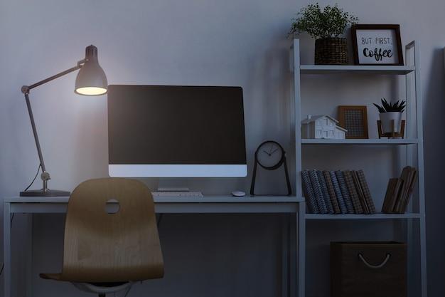 Lavoro di ufficio a casa di notte, con particolare attenzione alla scrivania del computer illuminata da una lampada fioca