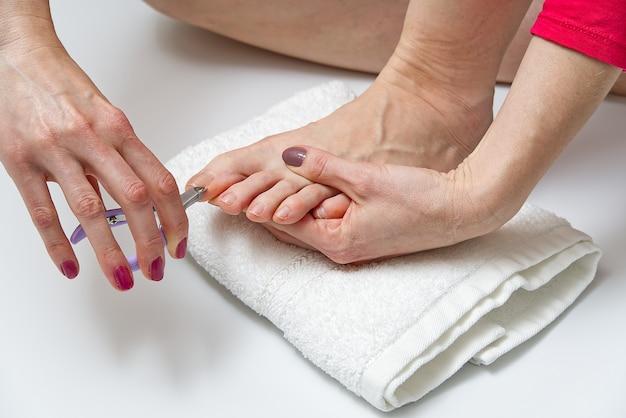 Pedicure a casa. trattamento di cura dei piedi e unghie. giovane donna che fa pedicure a casa.