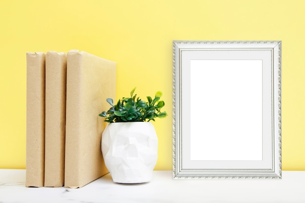 Pianta domestica in un vaso del cranio con i libri su una tavola vicino alla parete gialla
