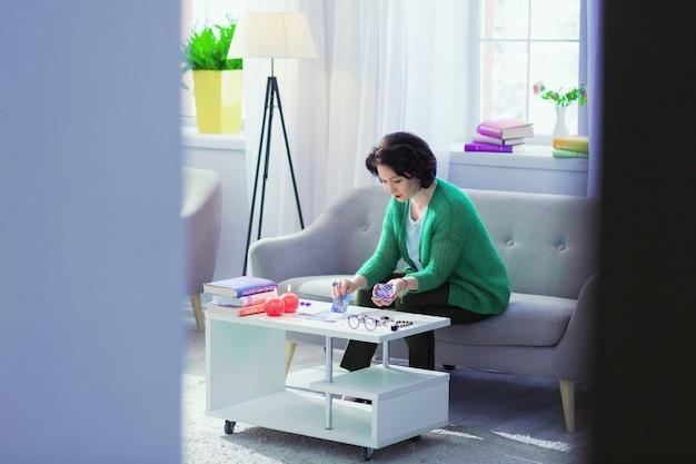 A casa. piacevole donna dai capelli scuri seduta sul divano mentre si utilizzano le carte dei tarocchi