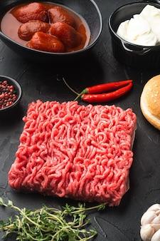 Home ingredienti per hamburger di polpette di carne macinata cruda, su tavola di pietra nera