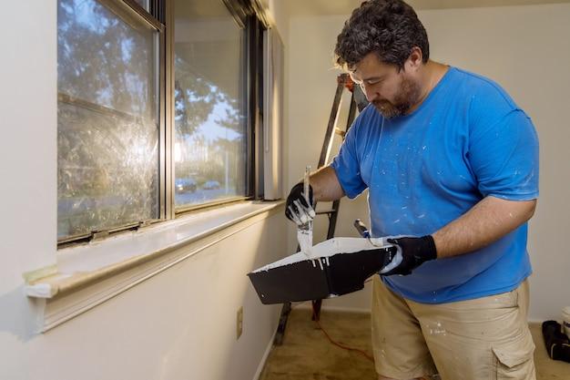 La ristrutturazione della casa nel tuttofare dipinge con uno strato di pennello di colore bianco una cornice di modanatura della finestra
