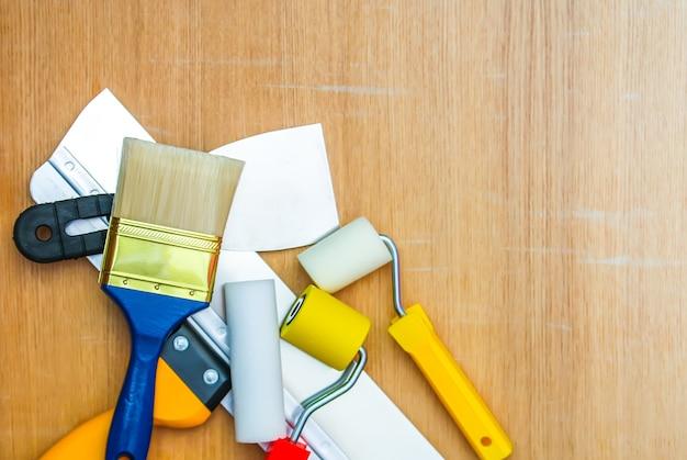 Strumenti di riparazione domestica su fondo di legno. rulli in gommapiuma e gomma per colorare le pareti e una spatola da vicino.