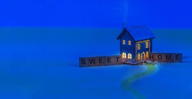 Concetto di strada di casa con casa giocattolo in piedi in un campo nel bel mezzo di una notte di notte