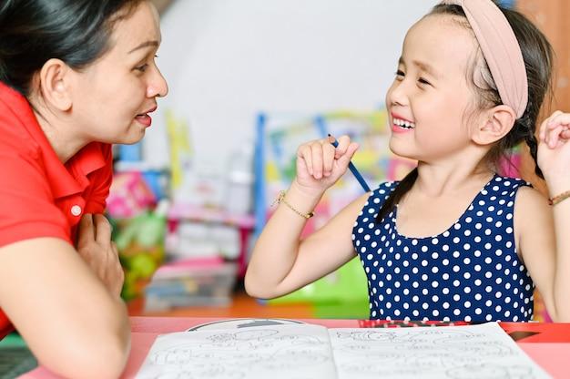 Il concetto di scuola domestica, i bambini asiatici e la madre insegnano a fare i compiti a scuola