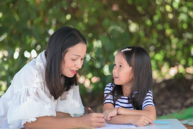 Il concetto di scuola domestica, la madre insegna ai bambini asiatici della figlia a fare i compiti di scuola nel giardino di casa o nel parco.