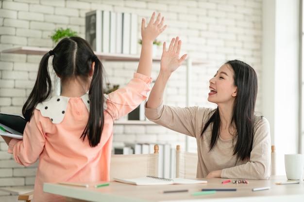 Scuola a casa che impara a casa durante la pandemia di virus. donna asiatica con sua figlia in soggiorno, che indossa maschere chirurgiche per proteggerli dal virus.