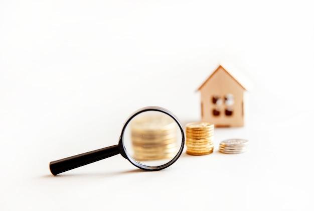 Lente di ingrandimento del concetto di ricerca domestica su sfondo bianco costruzione di alloggi in affitto ipotecario