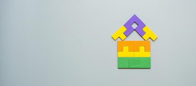 Blocco di forma domestica con pezzi di puzzle in legno colorato su grigio. pensiero logico, logica aziendale, soluzioni, concetti razionali, casa, immobiliare e strategia