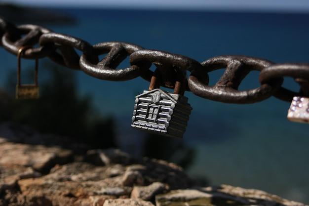 Lucchetto a forma di casa su una catena in riva al mare