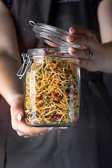 Vermicelli di pasta crudi colorati casalinghi in un barattolo di vetro