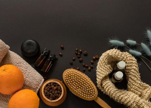 Concetto di casa spa. spazzola per il corpo, sapone, asciugamano, arance, chicchi di caffè e olio essenziale per massaggio anticellulite e trattamento della pelle sulla parete nera. design piatto. peeling domestico