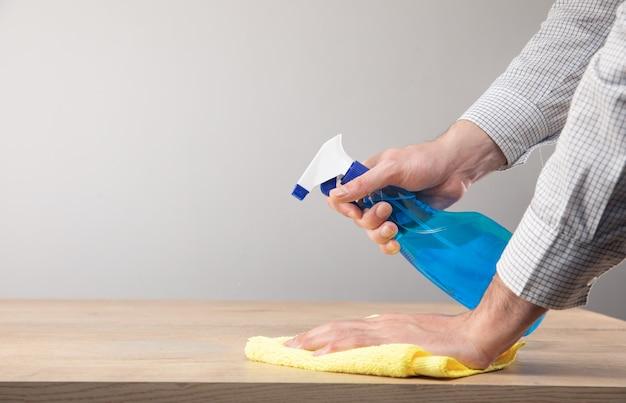 Pulizia della tavola domestica, disinfezione della superficie del tavolo con uno spray disinfettante