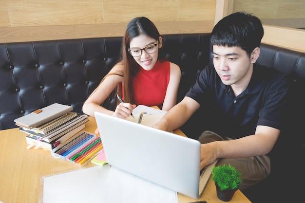 A casa, due studenti che lavorano su un progetto su un computer portatile, l'atmosfera è accogliente e calda.
