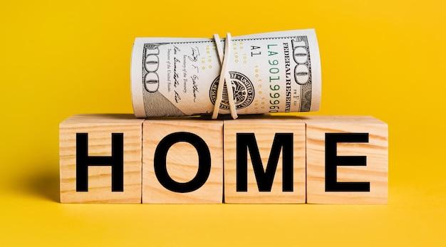 Casa con soldi su sfondo giallo. il concetto di affari, finanza, credito, reddito, risparmio, investimenti, cambio, tasse
