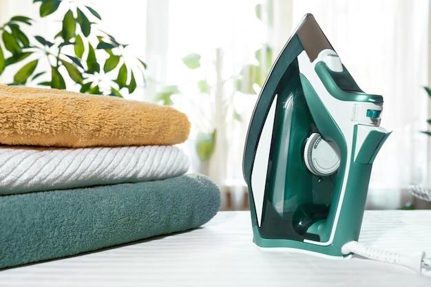 Home lavoro concetto verde vestiti di ferro e asciugamani sull'asse da stiro al chiuso