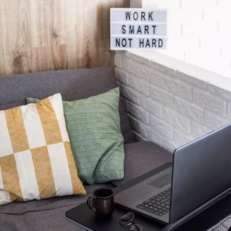 Luogo di lavoro domestico di un libero professionista ad un tavolo alla moda nero vicino al divano e muro di mattoni