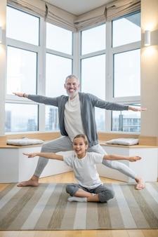 Yoga a casa. papà e i suoi figli fanno yoga insieme a casa e sembrano coinvolti