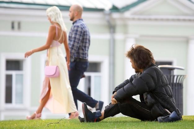 L'uomo senza casa osserva le persone che camminano