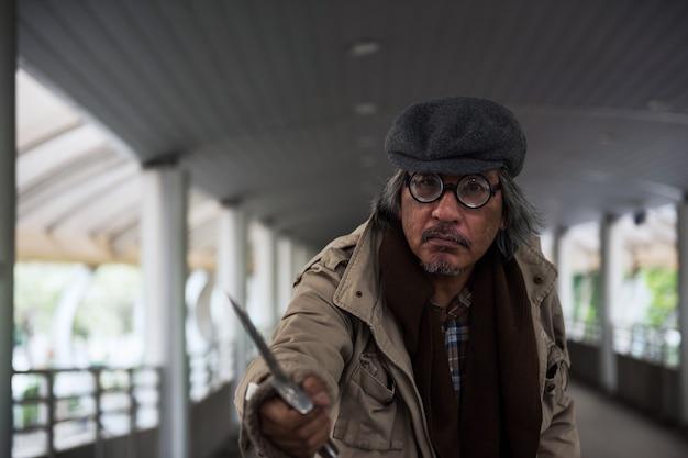 Il vecchio senzatetto minaccia puntando il coltello verso le persone che camminano nel cielo della città per rubare soldi. cattivo ladro che usa l'arma per rapinare.