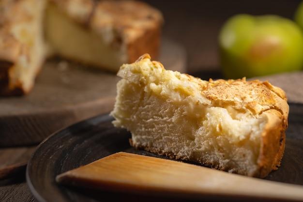 Fetta di torta di mele fatta in casa sul piatto di legno, ricetta facile da forno fatta in casa, messa a fuoco selettiva
