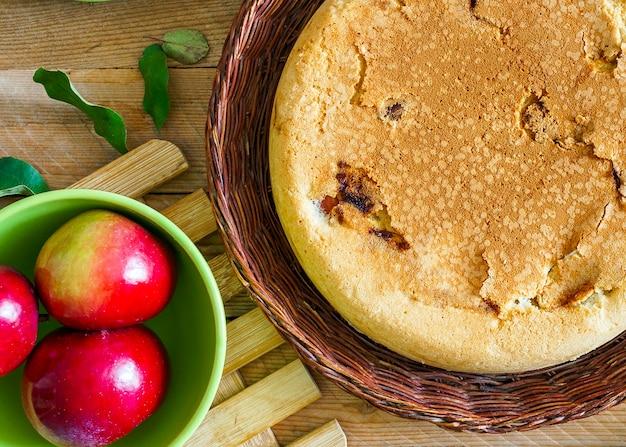 Torta di mele fatta in casa in un piatto di vimini su un tavolo di legno con ingredienti da cucina intorno