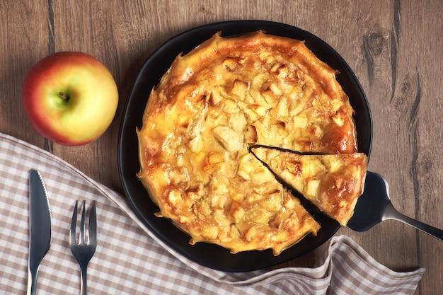 Torta di mele fatta in casa con mela e tovagliolo sul tavolo di legno
