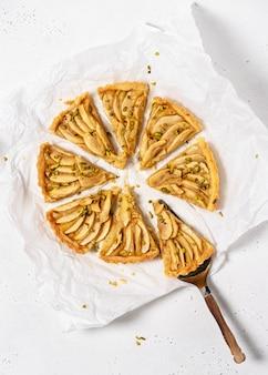 Crostata di mele fatta in casa pistacchi verdi e torta vintage su un foglio di carta da forno bianca