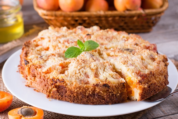 Torta di albicocche fatta in casa con frutta fresca sul tavolo in legno rustico