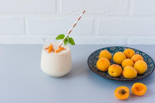 Frullato di albicocche fatto in casa e albicocche fresche. spuntino sano e delizioso.