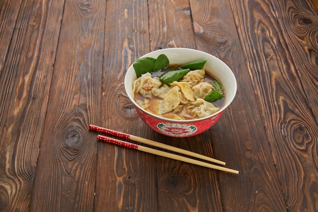 Zuppa di gnocchi wonton asiatici fatti in casa nella ciotola cinese rosso tradizionale con le bacchette di legno sopra la tavola di legno di struttura. vista dall'alto piatto laico, copia spazio asia cibo concetto