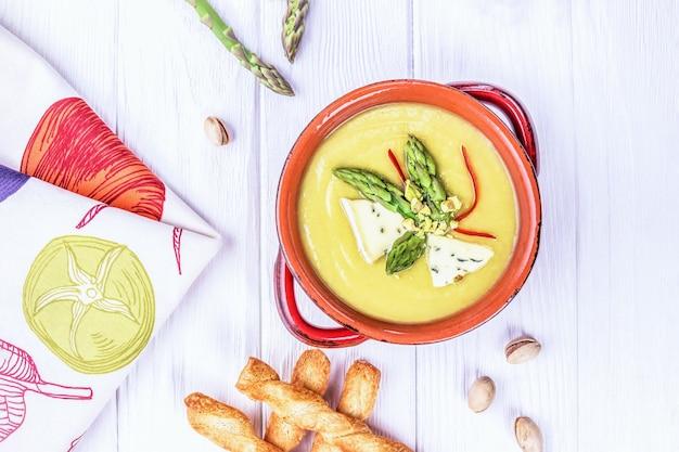 Zuppa di crema di asparagi fatta in casa con formaggio blu e pistacchi su un tavolo di legno bianco
