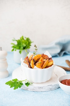 Patate fritte al forno fatte in casa con erbe e salsa rossa