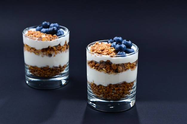 Muesli al forno fatto in casa con yogurt e mirtilli in un bicchiere su una superficie nera. spazio per testo o design.