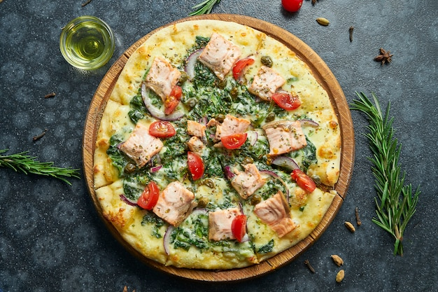 Pizza al forno fatta in casa con salmone, besciamella, spinaci, formaggio fuso, cipolle dolci e pomodori su una superficie nera in una composizione con ingredienti