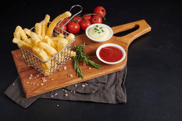 Patate fritte al forno fatte in casa con maionese, salsa di pomodoro e rosmarino su tavola di legno. gustose patatine fritte sul tagliere, in sacchetto di carta marrone su sfondo nero tavolo in pietra, cibo malsano.