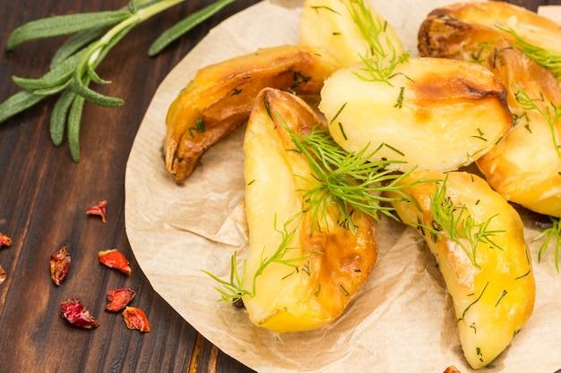 Patate fritte al forno fatte in casa con rosmarino su carta. lay piatto. avvicinamento