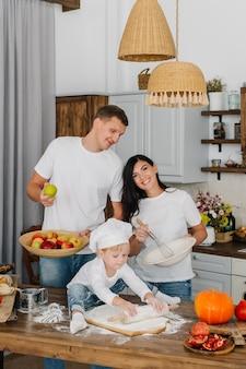 Concetto casalingo di festa di cottura. papà raccoglie le mele, la mamma dà fastidio all'impasto, un ragazzino carino gioca con la farina e stende la pasta in cucina.