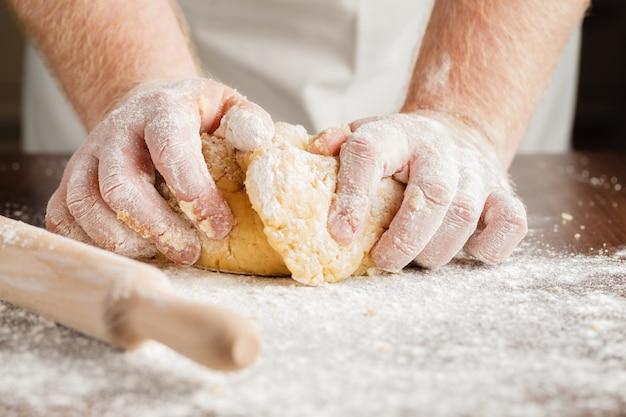 Cottura fatta in casa, scena della cucina che mostra burro, farina, zucchero e semi di vaniglia miscelati per fare biscotti di pasta frolla, con le mani dell'uomo.