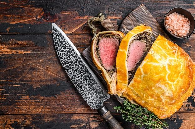 Torta di sfoglia alla wellington di manzo fatta in casa con filetto di carne su un tagliere