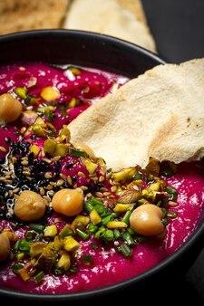 In casa di barbabietola e hummus di ceci con cruditãâ©s di verdure e pane azzimo su sfondo scuro