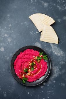Hummus di barbabietola fatto in casa in un piatto di ceramica nera sul vecchio fondo di cemento scuro. messa a fuoco selettiva. vista dall'alto.