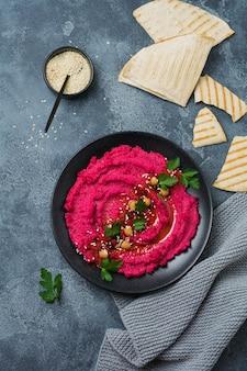 Hummus di barbabietola fatto in casa in un piatto di ceramica nera